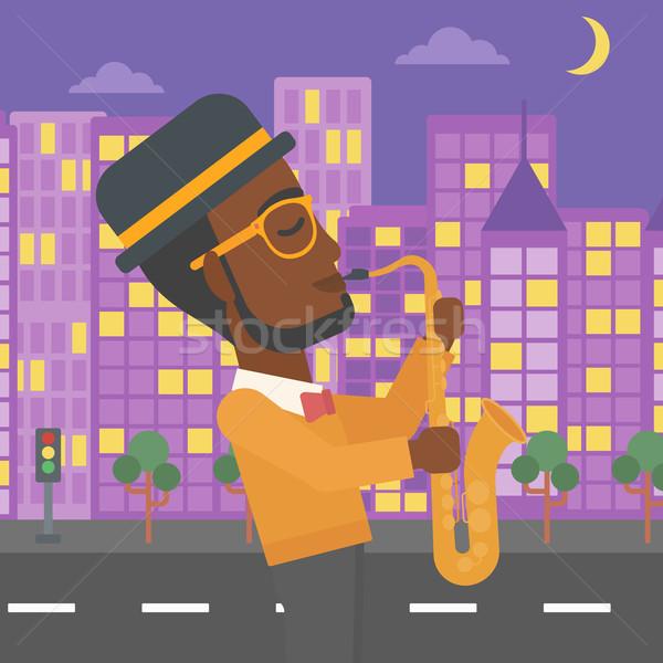 Zenész játszik szaxofon férfi éjszaka város Stock fotó © RAStudio
