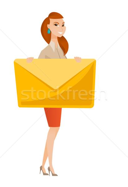 Smiling business woman holding a big envelope. Stock photo © RAStudio