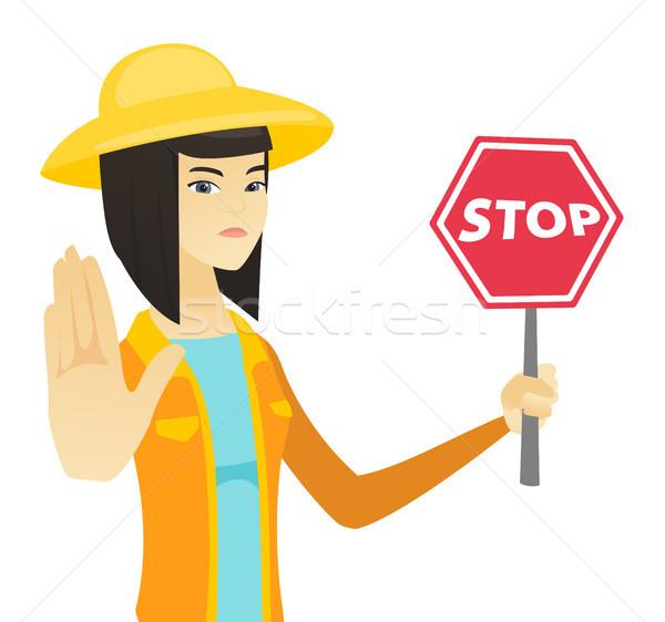Young asian farmer holding stop road sign. Stock photo © RAStudio