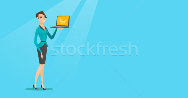 Woman holding laptop with trolley on a screen. Stock photo © RAStudio