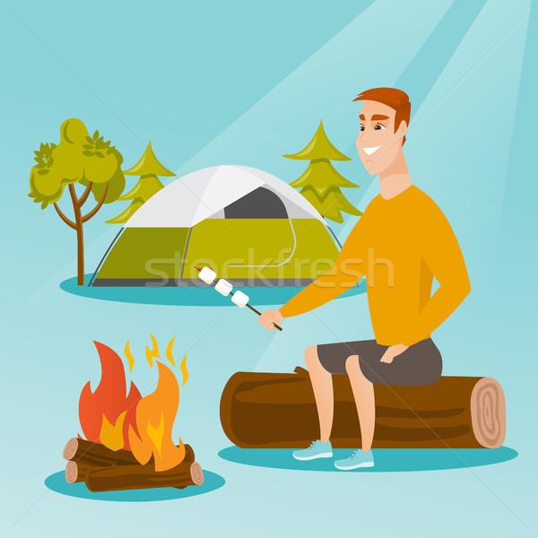 Caucasian man roasting marshmallow over campfire. Stock photo © RAStudio