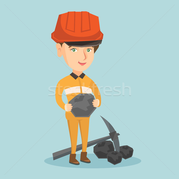 Young miner in hard hat holding a piece of coal. Stock photo © RAStudio