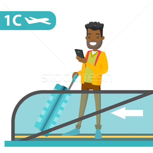 A traveller in an airport with a smartphone and a suitcase. Stock photo © RAStudio