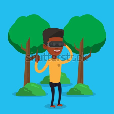 Woman wearing virtual reality headset in the park. Stock photo © RAStudio