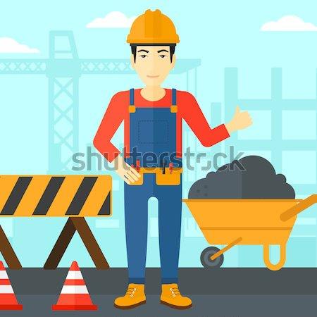 Young hispanic builder using pneumatic hammer. Stock photo © RAStudio