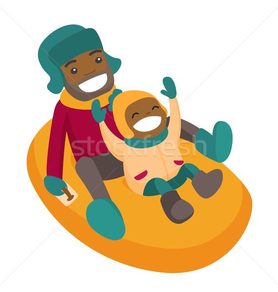 Father with son sledding down on snow rubber tube. Stock photo © RAStudio