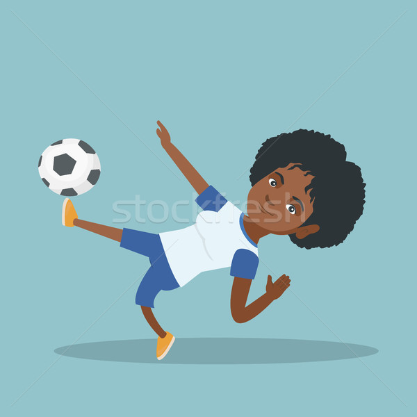 Young african soccer player kicking a ball. Stock photo © RAStudio