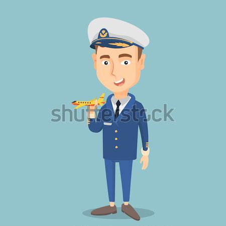 Cheerful airplane pilot with model of airplane. Stock photo © RAStudio