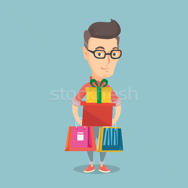 Happy man holding shopping bags and gift boxes. Stock photo © RAStudio
