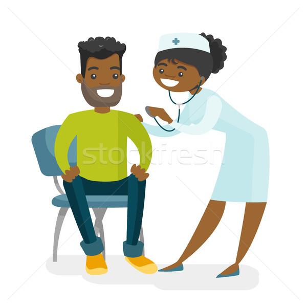 African doctor listening to the heart of patient. Stock photo © RAStudio