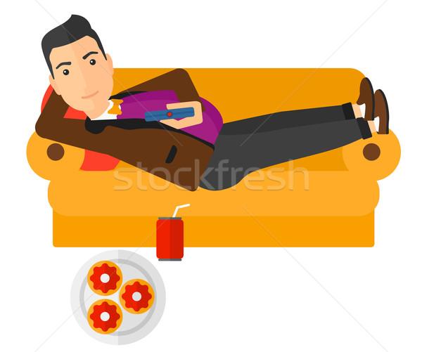 Człowiek sofa pilota strony Zdjęcia stock © RAStudio