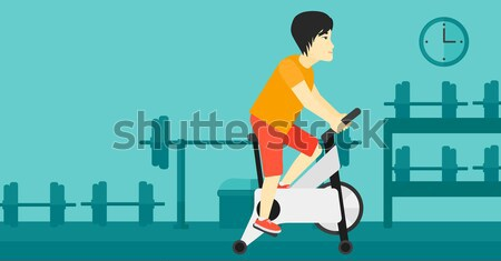 Woman riding stationary bicycle. Stock photo © RAStudio