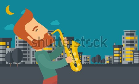 Saxophonist playing in the streets at night Stock photo © RAStudio
