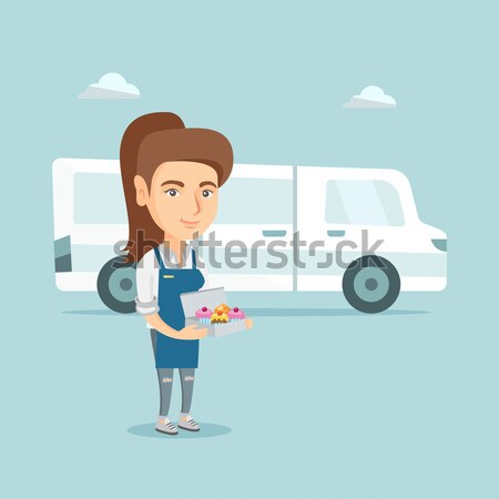Delivery man holding a box of cakes. Stock photo © RAStudio