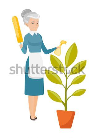 African housemaid watering the flower with spray. Stock photo © RAStudio