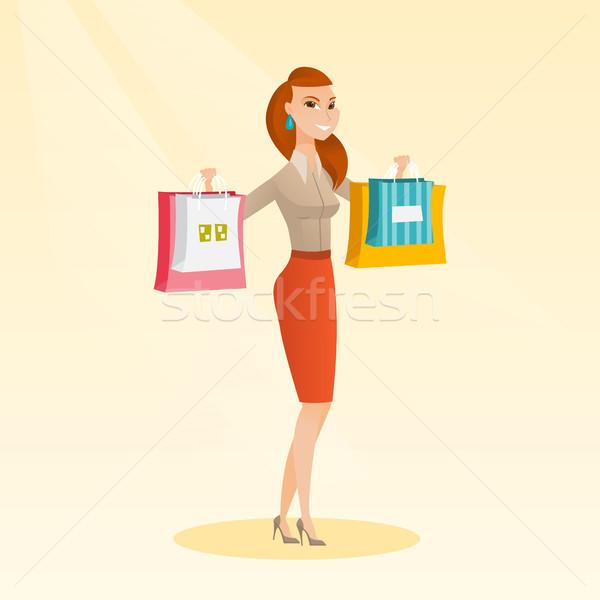 Young caucasian woman holding shopping bags. Stock photo © RAStudio