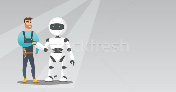 Young caucasian man handshaking with robot. Stock photo © RAStudio