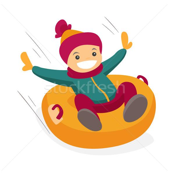 Caucasian boy sledding down on snow rubber tube. Stock photo © RAStudio