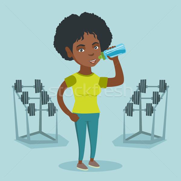 Young african-american sportswoman drinking water. Stock photo © RAStudio