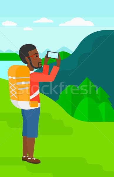 Mochilero toma foto hombre paisaje montanas Foto stock © RAStudio