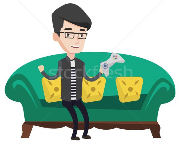 Férfi játszik videojáték boldog kaukázusi ül Stock fotó © RAStudio
