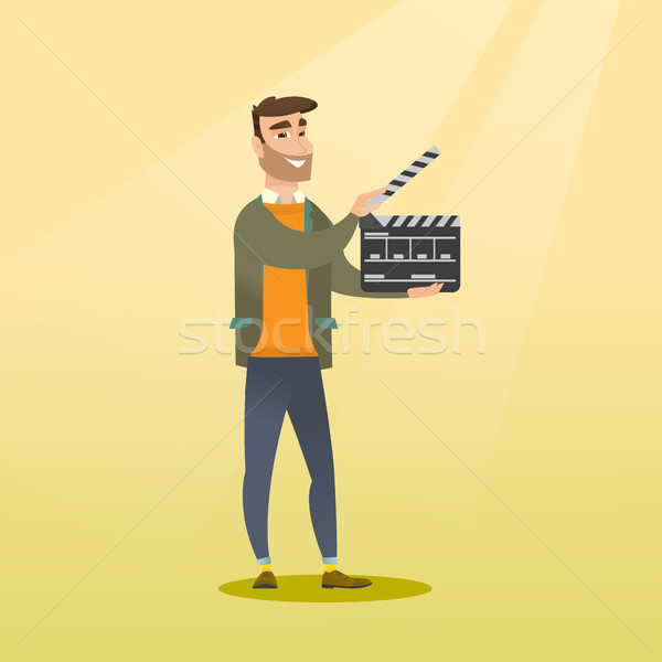Smiling man holding an open clapperboard. Stock photo © RAStudio