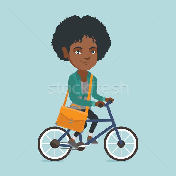 Young african business woman riding bicycle. Stock photo © RAStudio