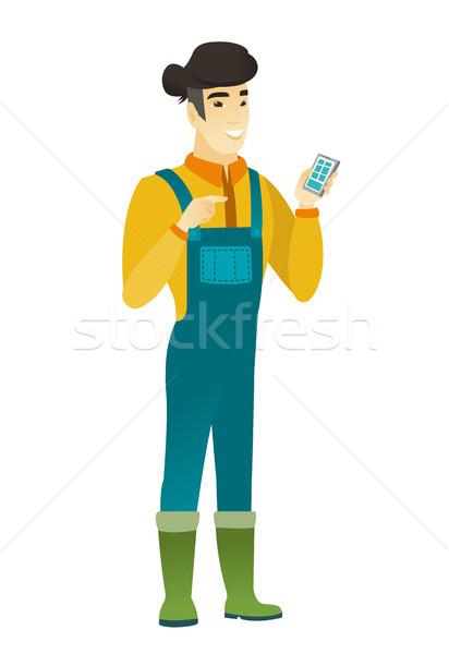 Asian farmer holding a mobile phone. Stock photo © RAStudio