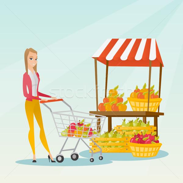 Young caucasian woman pushing a supermarket cart. Stock photo © RAStudio