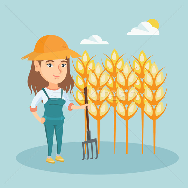 Young farmer standing in a field with pitchfork. Stock photo © RAStudio