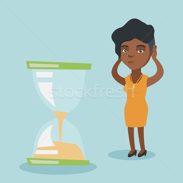 Zdesperowany business woman patrząc klepsydry młodych Afryki Zdjęcia stock © RAStudio