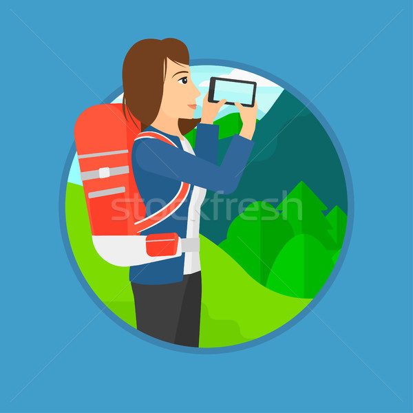 Woman with backpack taking photo. Stock photo © RAStudio