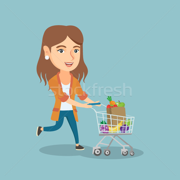 Caucasian woman running with a shopping trolley. Stock photo © RAStudio