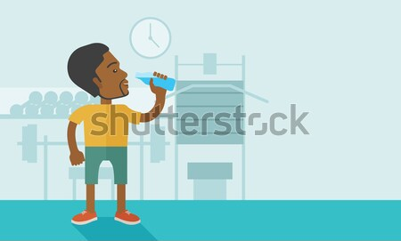 Gentleman drink a bottle of water while inside the gym. Stock photo © RAStudio