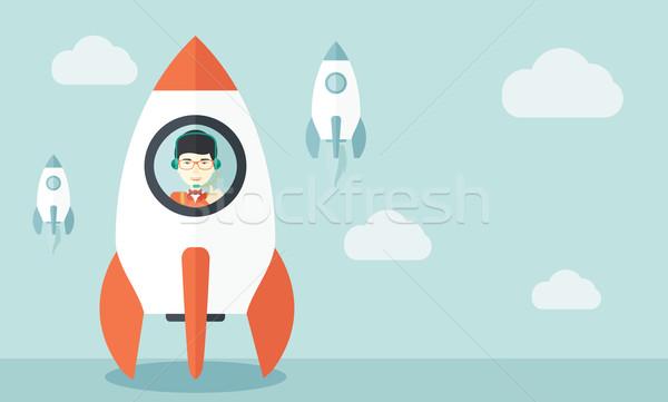 Genç Asya adam yan roket içinde Stok fotoğraf © RAStudio