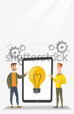 Two businessman holding a big tablet with bulb symbol Stock photo © RAStudio