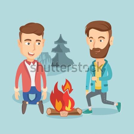 Foto stock: Dois · amigos · sessão · em · torno · de · fogueira · camping