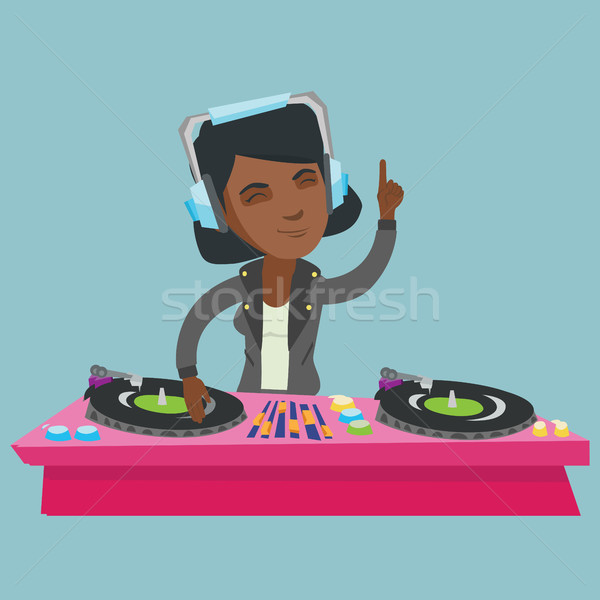 Young african DJ mixing music on turntables. Stock photo © RAStudio