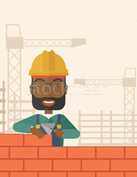 Black builder man is building a brick wall. Stock photo © RAStudio
