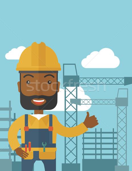 Black man standing infront of construction crane tower. Stock photo © RAStudio
