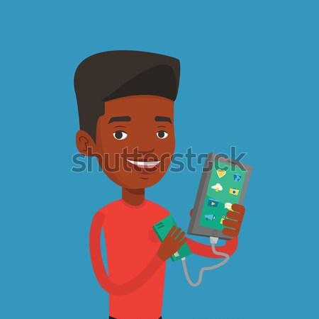 Człowiek smartphone przenośny baterii Afryki telefonu komórkowego Zdjęcia stock © RAStudio