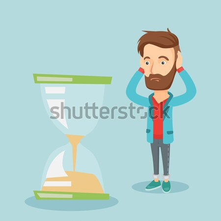 Desperate business man looking at hourglass. Stock photo © RAStudio