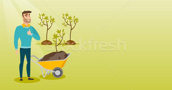 Man pushing wheelbarrow with plant. Stock photo © RAStudio