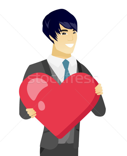Young asian groom holding a big red heart. Stock photo © RAStudio