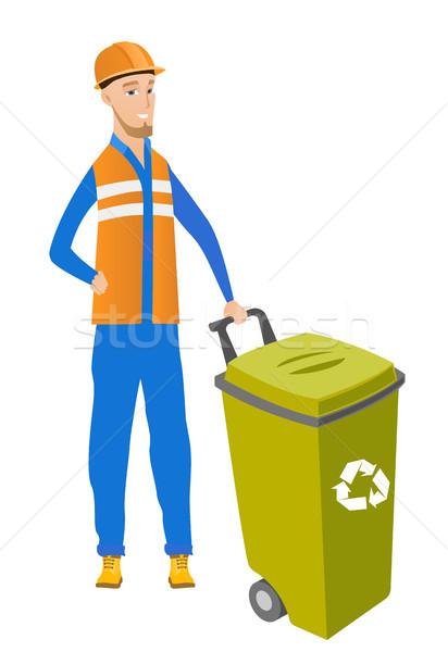 Young caucasian builder pushing recycle bin. Stock photo © RAStudio