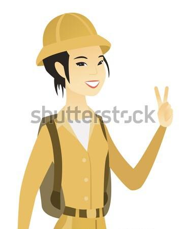 Young asian traveler waving her hand. Stock photo © RAStudio