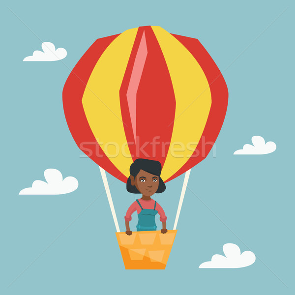 Stock photo: Young african woman flying in hot air balloon.