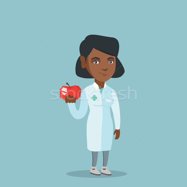 Young african nutritionist offering an apple. Stock photo © RAStudio