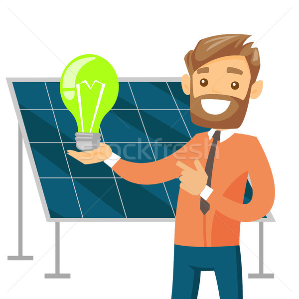 Engineer of solar power plant holding lightbulb. Stock photo © RAStudio