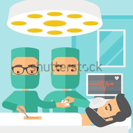 Due chirurghi guardando paziente sala operatoria contemporanea Foto d'archivio © RAStudio